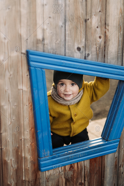 Happy baby looking through window in a tree house at a park