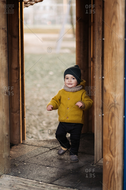 Baby playing in a tree house structure at a park