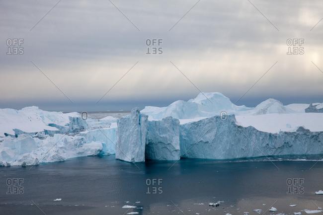 Icebergs under gray cloudy skies on the coast of Ilulissat, Greenland
