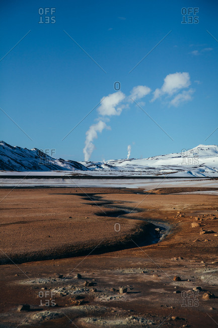 River leading through field toward snowy mountains in Iceland