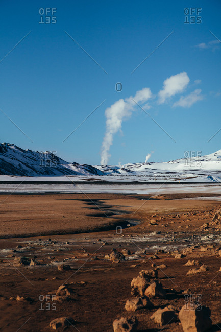 Vast dirt field and snowy mountains in Iceland