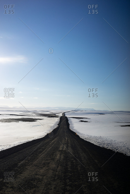 Long dirt road surrounded by snow in Iceland