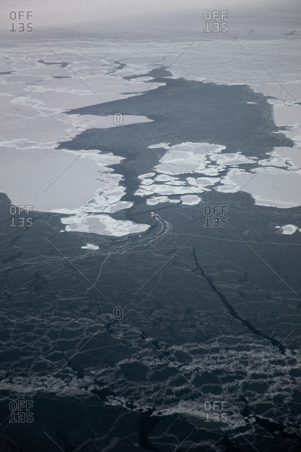 Aerial view of boat navigating through icy waters
