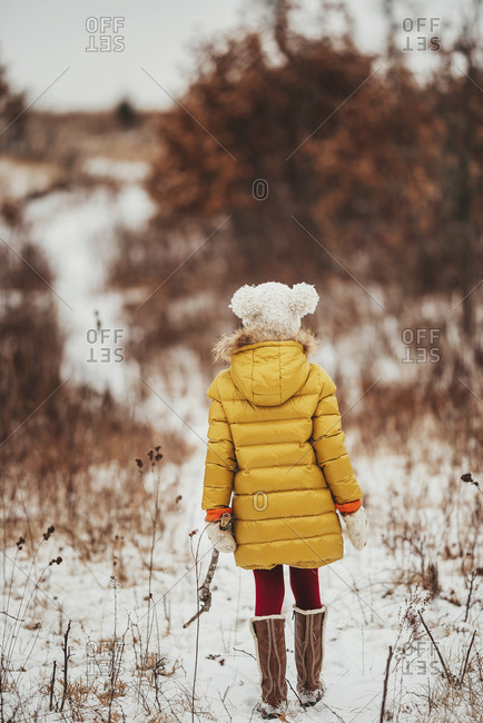 Rear view of a little girl in a yellow coat walking in the snow