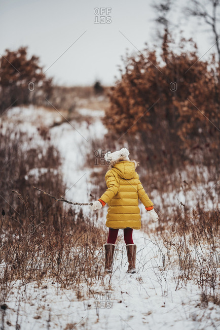 Rear view of a little girl in a yellow coat walking in the snow with a stick