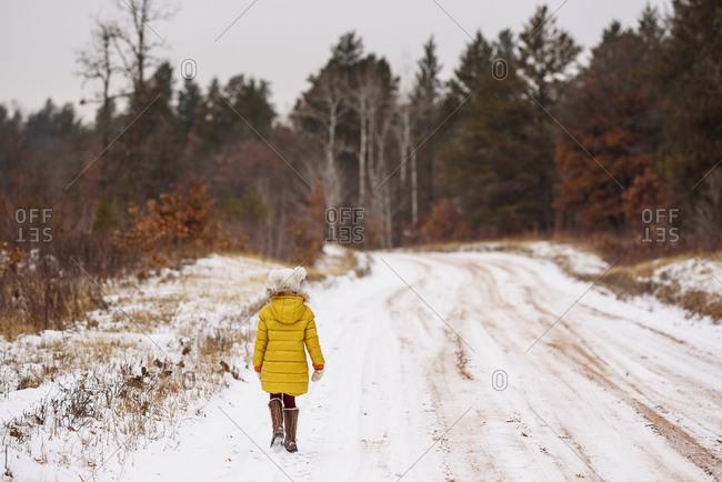 Rear view of a little girl in a yellow coat walking on snowy road