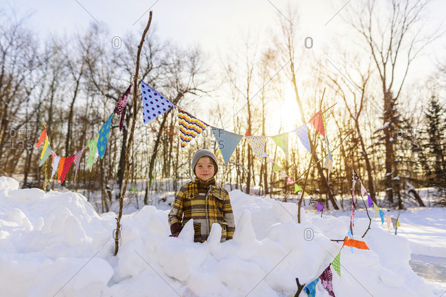 Portrait of a young boy playing in a snow fort