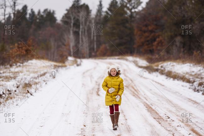 Little girl in a yellow coat walking on snowy road