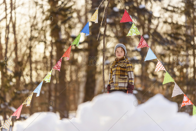 Portrait of a young boy playing in a snow fort in winter