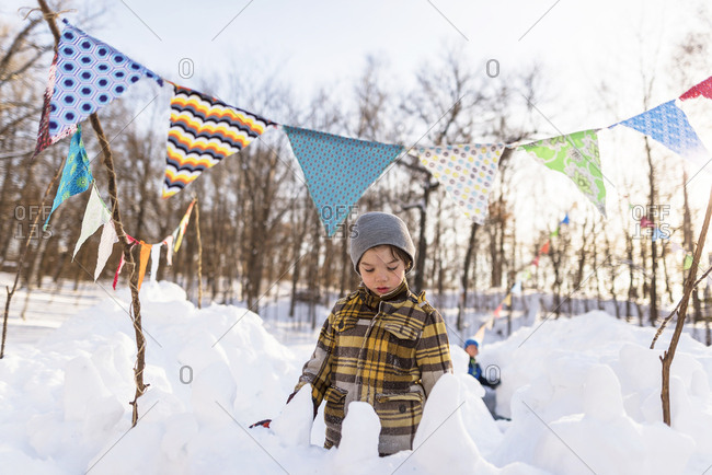 Young boy playing in a snow fort
