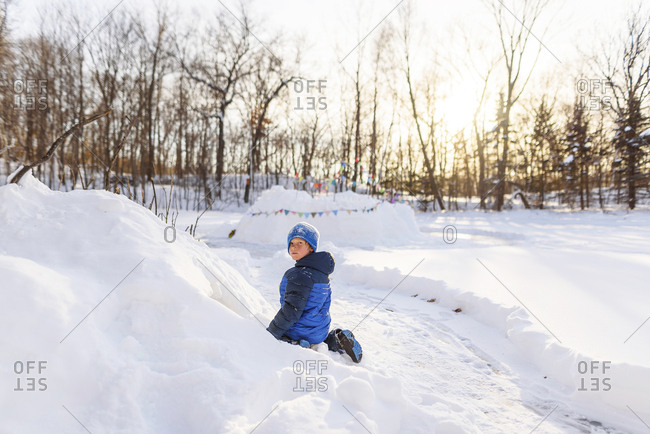 Young boy playing in a snow fort at sunset