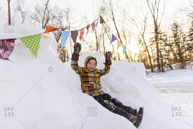 Happy young boy playing in a snow fort