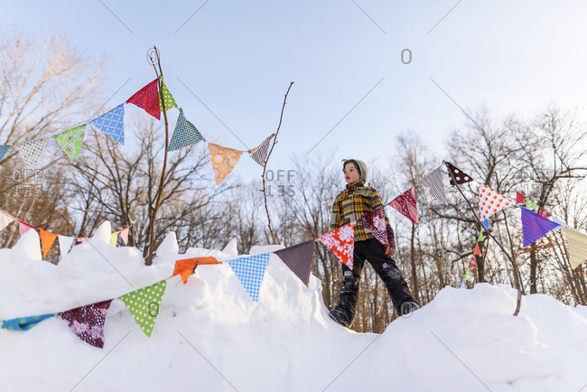 Young boy standing at the top of a snow fort