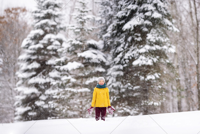 Portrait of a young girl outside playing in deep snow