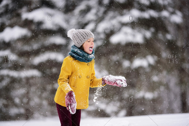 Young girl outside eating snow