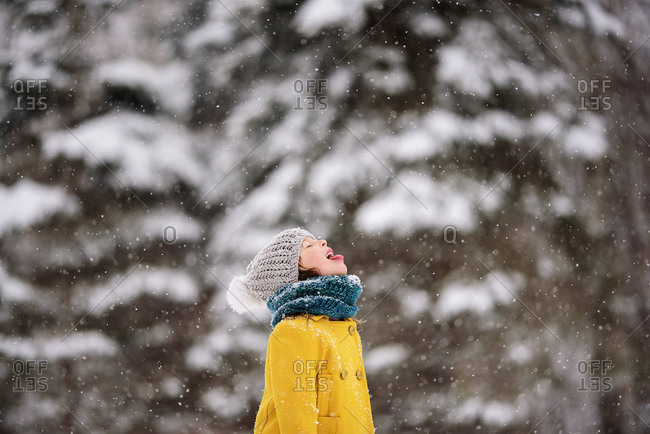 Young girl outside catching snowflakes on her tongue