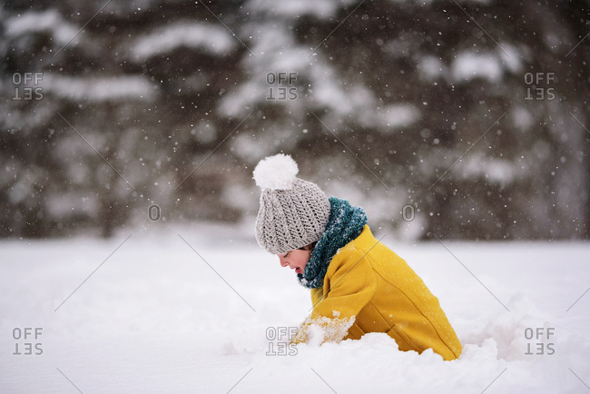 Happy little girl playing outside during a snowfall