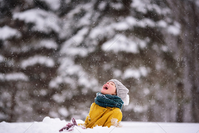 Little girl outside catching snowflakes on her tongue