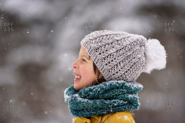 Portrait of a smiling young girl outside during a snowfall