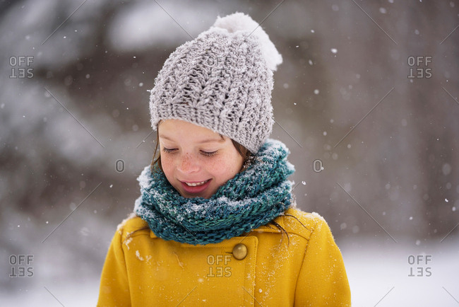 Portrait of a happy young girl outside during a snowfall