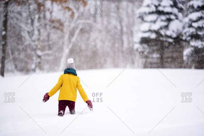 Rear view of young girl outside playing in deep snow