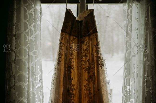 Lacy wedding gown hanging in window with view of snow outside