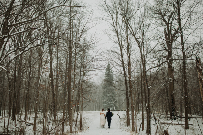 Couple walking hand in hand through snowy forest on their wedding day