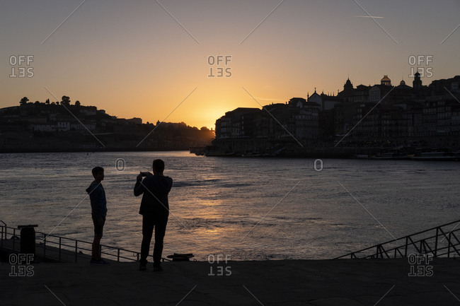 Porto, Portugal - 11 August 2018: People watching sunset over Douro river
