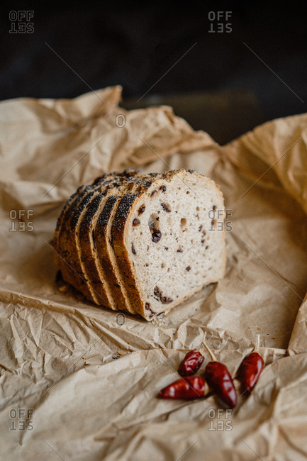 Slices of tasty sweet bread with poppy seeds lying on piece of parchment paper
