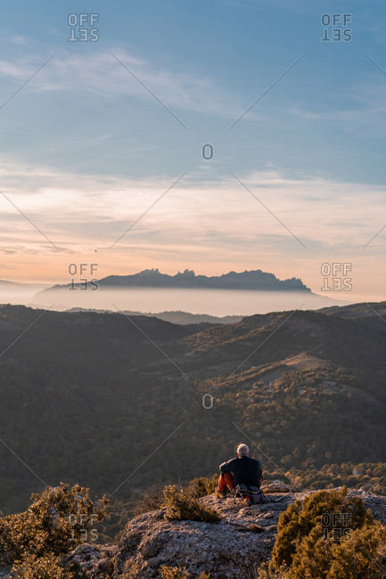 Back view of elderly man in casual outfit sitting on rocky cliff and admiring view of majestic mountains and beautiful evening sky