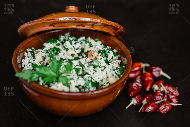 Heap of red hot chili peppers lying near ceramic bowl with tasty curd with herbs on dark tabletop