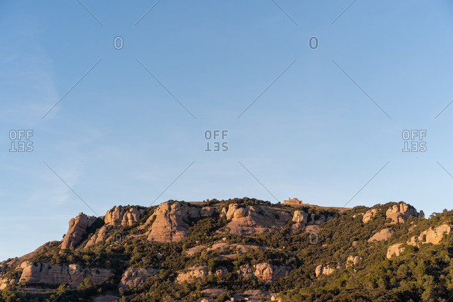 Beautiful view of cloudless blue sky over rough mountain cliff on sunny day
