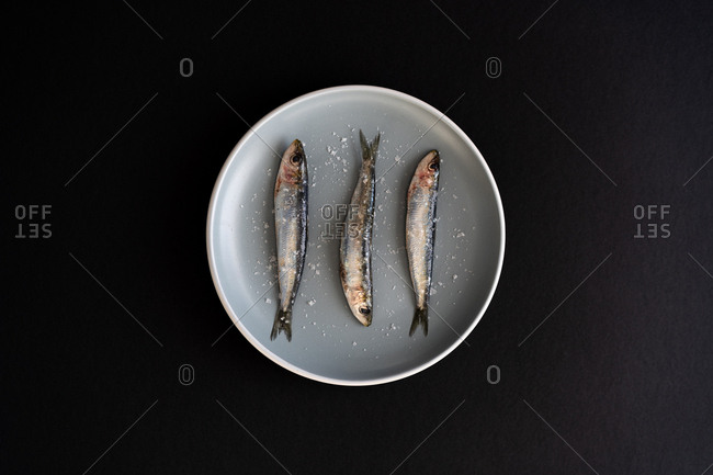Three small salty anchovies lying on ceramic plate on black background