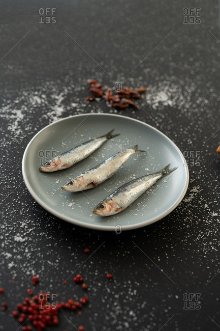 Assorted spices lying on black background around ceramic plate with tasty salty anchovies