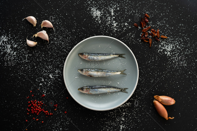 Bunch of cherry tomatoes and assorted spices lying on black background around ceramic plate with tasty salty anchovies