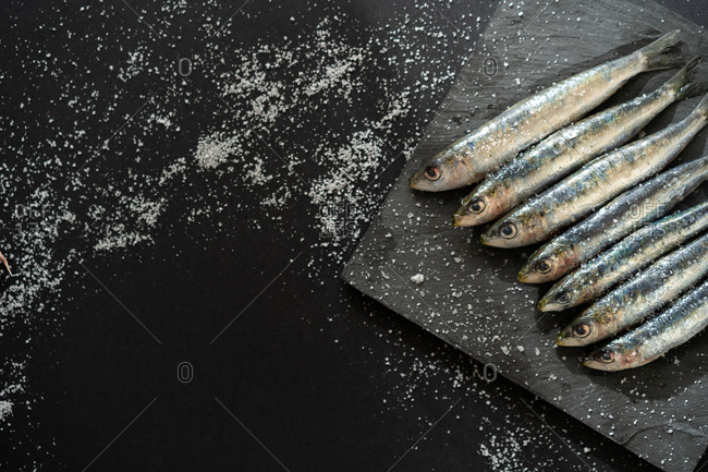 Square board with set of fresh anchovies lying on black background