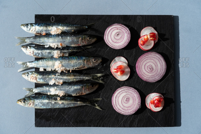 Fresh anchovies lying on black board near slices of ripe onion with radish and pomegranate seeds on gray background