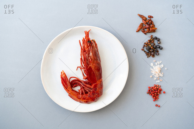 Set of assorted spices lying near plate with tasty boiled prawn on blue background