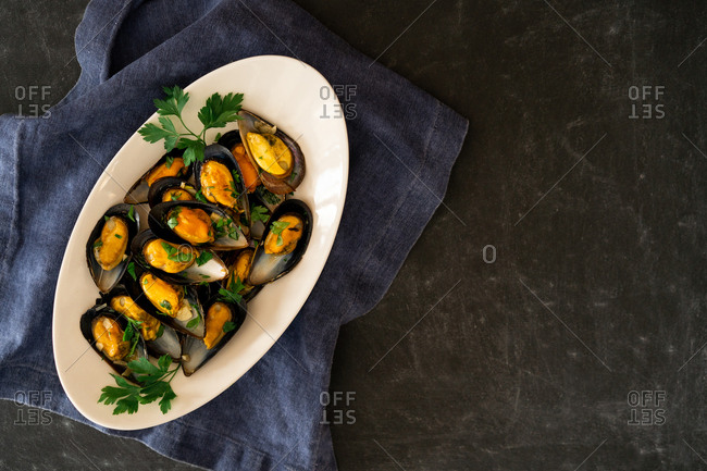 Ceramic plate with yummy boiled mussels standing on piece of cloth on gray background