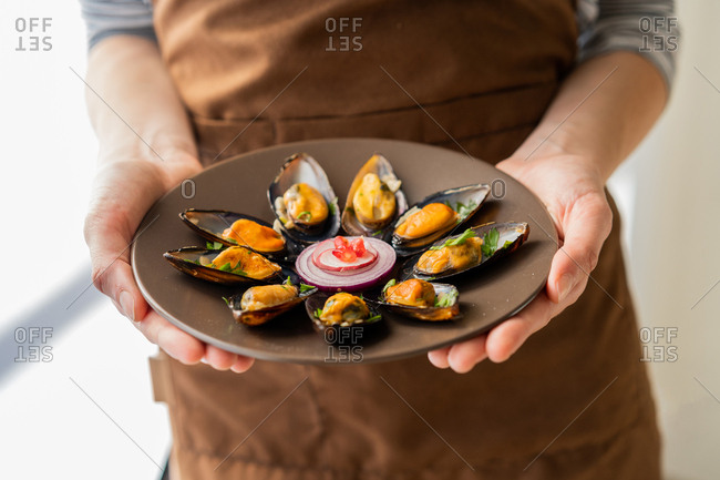Unrecognizable female holding ceramic plate with portion of palatable boiled mussels