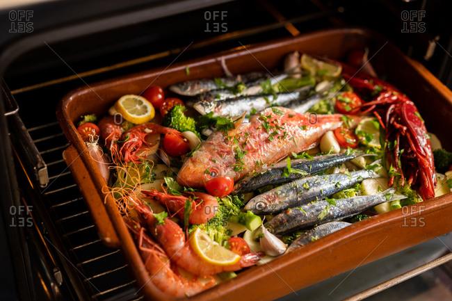 Closeup shot of ceramic pan of delicious dish with fish and prawns