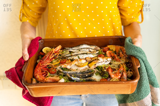 Hands of anonymous woman taking ceramic pan with tasty seafood dish from hot oven at home