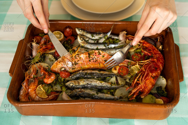 Hands of anonymous female using fork and knife to take delectable seafood dish from ceramic pan on table