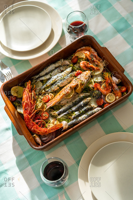 Pan with palatable seafood dish and glasses of red wine standing on checkered tablecloth
