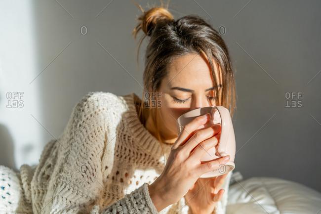 Woman with mug on bed
