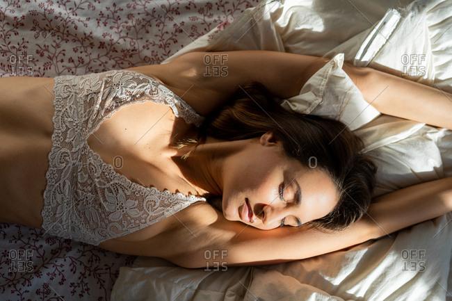 Woman in bra lying on bed