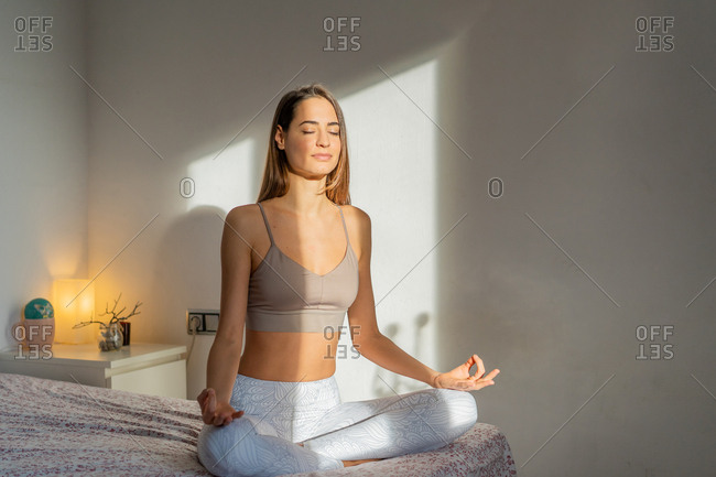Beautiful young female in sportswear keeping eyes closed and meditating while sitting in lotus pose on comfortable bed in morning