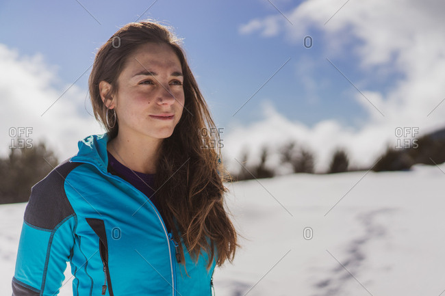 Beautiful young female in warm clothes smiling and looking away while standing on blurred background of majestic winter nature on sunny day