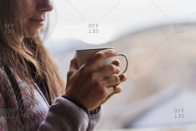 Side view of unrecognizable female in warm jumper smiling and enjoying hot beverage while standing near huge window at home
