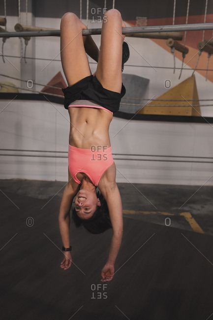 Young slim sportive lady in sportswear with legs on horizontal bar doing exercises in gym